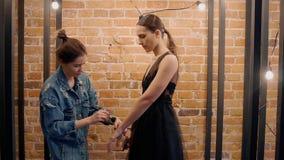 一位专业化妆师做在一套黑婚礼礼服的构成模型 反对红砖背景和 股票视频