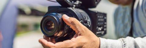 一位专业摄影师在射击横幅前准备一台照相机和一个三脚架,长的格式 库存照片