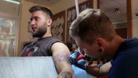 一位专业纹身花刺艺术家在一条人` s胳膊做纹身花刺在纹身花刺客厅里 股票录像