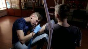 一位专业纹身花刺艺术家在一条人` s胳膊做纹身花刺在纹身花刺客厅里 影视素材
