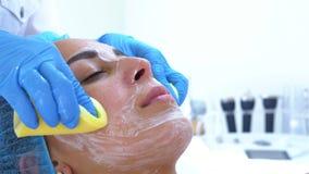 一位专业美容师和皮肤病学家在使用治疗面具以后清洗妇女的面孔与黄色海绵 皮肤tighte 股票录像