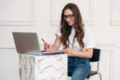 一位俏丽的女孩自由职业者为膝上型计算机在纸和微笑工作,写笔记,计划她的工作天 一名妇女以黑暗 库存图片