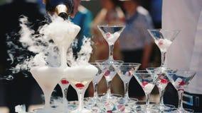 一位典雅的侍者的手倒在泡沫玻璃的香槟 从玻璃是白色烟和浪花 户外 影视素材
