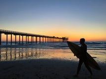 一位冲浪者的剪影斯克里普斯码头的在拉霍亚,加利福尼亚 库存照片