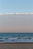 一位冲浪者的剪影的金黄日落光他的移动朝海的委员会的在与沙子和没有云彩的海滩在s 库存图片