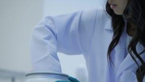 一位医学研究科学家的特写镜头去掉有实验解答液体的玻璃瓶从低温