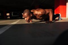 一位半赤裸被集中的肌肉美国黑人的运动员的画象 免版税库存照片