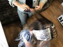 一位单独企业家在家提供服务 美发师绘妇女的头发 免版税图库摄影