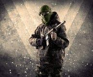 一位危险被掩没的武装的战士的画象有脏的backgro的 库存照片