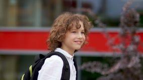 一位卷曲蓝眼睛的男小学生的画象的关闭 男孩摇他的手并且笑 愉快的男小学生,回到学校 股票录像