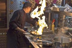 一位厨师在旅馆在烹调显示他的精采技术给访客在Ha Noi城市 免版税图库摄影