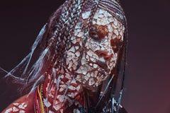 一位可怕非洲僧人女性的画象有石化破裂的皮肤和dreadlocks的 构成概念 库存照片