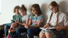 一位可爱的女小学生读一本书,当坐长凳在她的同学旁边时 其他孩子使用与他们 影视素材
