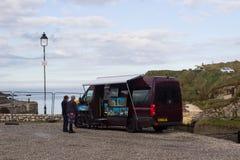 一位地方艺术家使用他的贸易与一名潜在的顾客在港口在Ballintoy在北爱尔兰 图库摄影