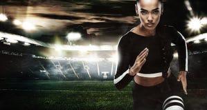 一位坚强的运动,妇女短跑选手,跑在佩带在运动服、健身和体育刺激的staidum 赛跑者 免版税库存照片