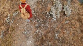 一位女孩摄影师的特写镜头空中顶视图一个黄色帽子的有沿山道路去的背包的 ?? 股票视频