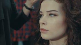 一位女孩美发师投入一双黑眼睛遮蔽一个深色的模型的眼皮 股票视频
