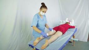 一位女性化妆师在懒散以后将润湿客户` s腿的皮肤 影视素材