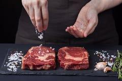 一位女性厨师洒海盐与从使有大理石花纹的牛肉的两块新鲜的未加工的ribeye牛排在黑暗的背景 附近p混合物  免版税库存照片