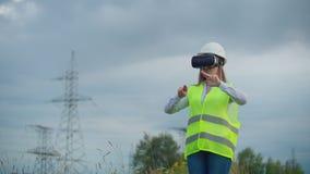 一位女性工程师处理可选择能源传输从太阳电池板和风力场的给消费者  股票录像