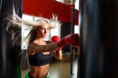 一位女性拳击手在戴着红色手套的健身房训练 免版税库存图片