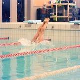 一位女性游泳者,那跳进和潜水室内运动游泳池 运动的妇女 库存图片