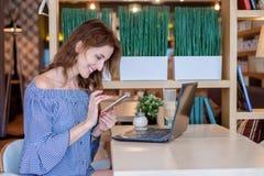 一位女性自由职业者在电话谈话,当在与一台便携式计算机的一个咖啡馆坐桌时 有吸引力的年轻人 免版税库存照片