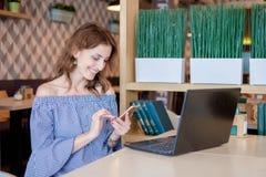 一位女性自由职业者在电话谈话,当在与一台便携式计算机的一个咖啡馆坐桌时 有吸引力的年轻人 库存照片