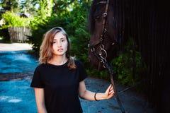 一位女性,黑黑白花的公马纯血种马宠物的情感画象爱上马的 免版税库存照片