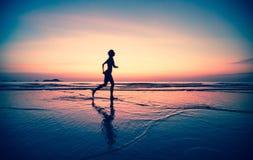 一位妇女慢跑者的Blured剪影在海滩的在日落 免版税库存图片