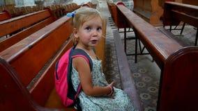 一位小天主教徒在一个老空的教会里单独坐 股票视频
