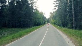 一位小姐的跑步的过程沿森林胡同的 影视素材