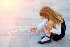 一位小逗人喜爱的女小学生画在爱妈妈边路的五颜六色的白垩  免版税库存图片