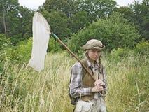 一位少妇昆虫学家在乡村模式穿戴了与在领域的昆虫网 库存图片