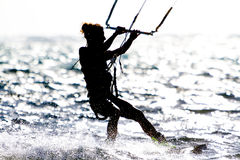 一位少妇风筝冲浪者乘坐反对太阳 图库摄影