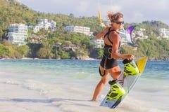 一位少妇风筝冲浪者准备好在蓝色s的风筝冲浪的乘驾 库存图片
