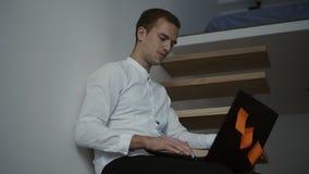 一位年轻专业人自由职业者的侧视图白色衬衣的使用便携式计算机,当下来坐现代时 股票录像