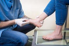 一位年轻人医生骨科医师的手举办诊断,一名妇女的脚脚测试的个体制造或者 免版税库存照片