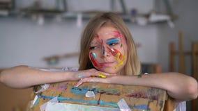 一位年轻可爱的艺术家的画象有油漆的在她的面孔,倾斜在画架 股票录像