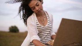 一位年轻女性艺术家的出色的意见在户外工作过程中 使用调色板和画架的油漆 挥动她的风卷曲 股票视频