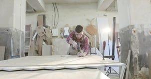 一位年轻木匠在木材加工工厂工作 股票录像