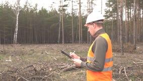 一位年轻白种人男性审查员写下森林和砍伐森林,风景 股票视频