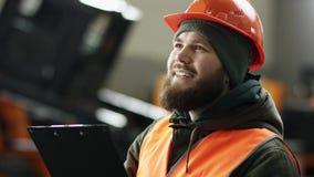 一位年轻美丽的汽车修理师的画象在一个汽车车间,在服务背景中  他进入在a的一个车库 影视素材