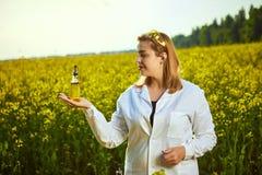 一位年轻美丽的生物学家或农艺师审查菜子油的质量在强奸领域的 r 免版税库存图片