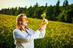 一位年轻美丽的生物学家或农艺师审查菜子油的质量在强奸领域的 r 免版税图库摄影