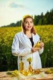 一位年轻美丽的生物学家或农艺师审查菜子油的质量在强奸领域的 r 免版税库存照片