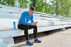 一位年轻肌肉运动员在立场坐并且听到音乐在训练以后 免版税库存图片