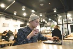 一位年轻自由职业者为在一个豪华的咖啡馆的一台膝上型计算机工作并且喝咖啡 一台计算机的行家学生在咖啡馆 库存照片