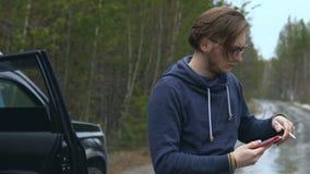 一位年轻艺术家在路和油漆站立在片剂 股票录像