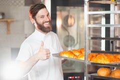 一位年轻英俊的面包师在他的手显示他的与新鲜的新月形面包板料的赞许反对烤箱的背景 免版税库存照片